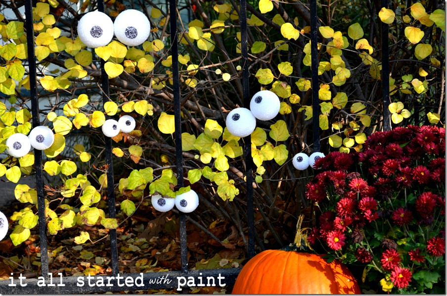eyes-on-fence-for-halloween-with-pumpkin