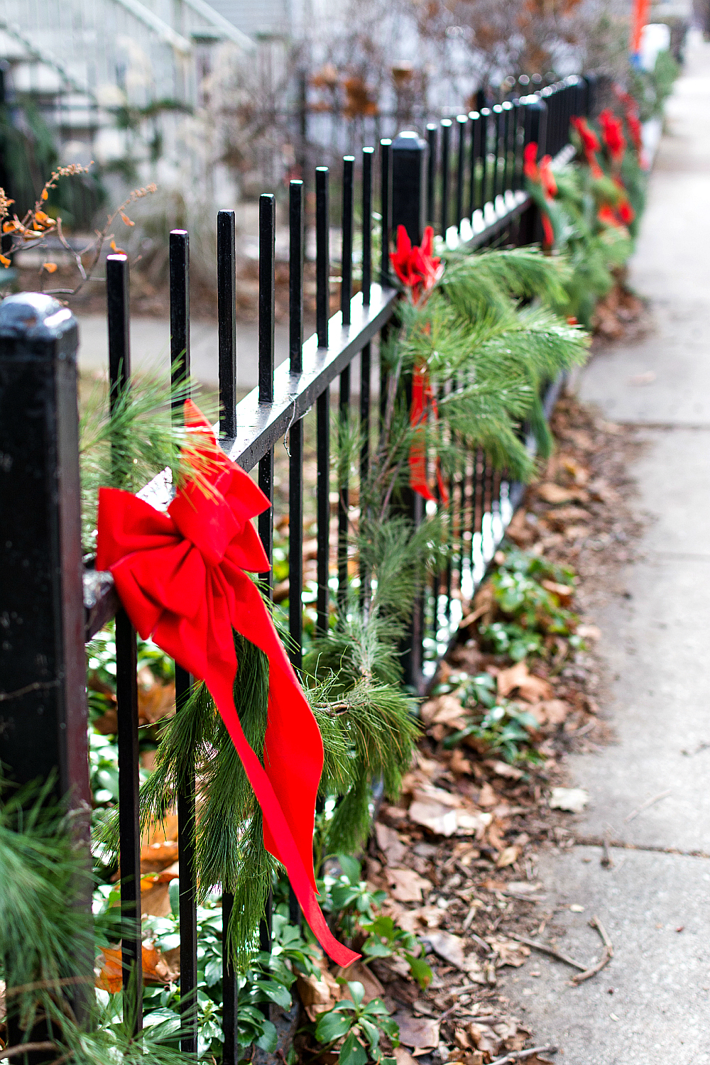 iron fence with garland and bows in chicago - Christmas Decorations Bows