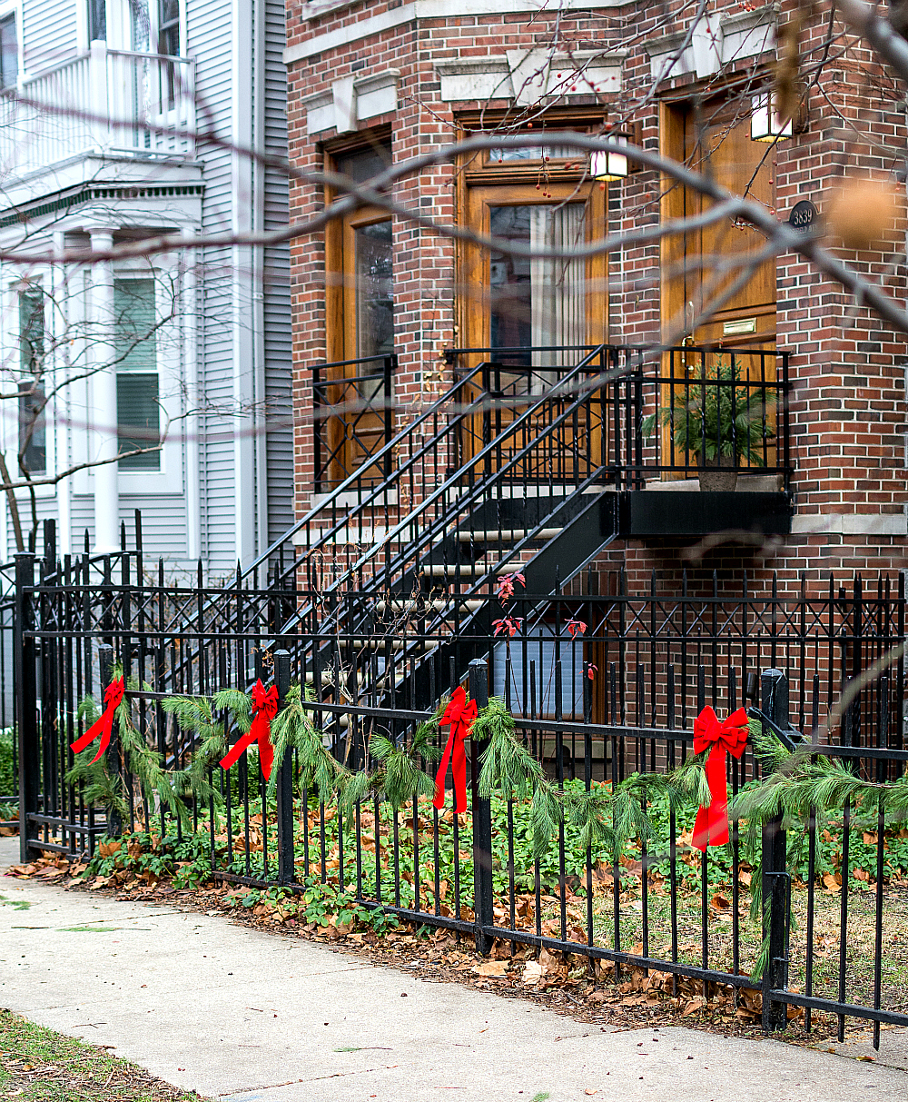 iron fence decorated with garland and red bows