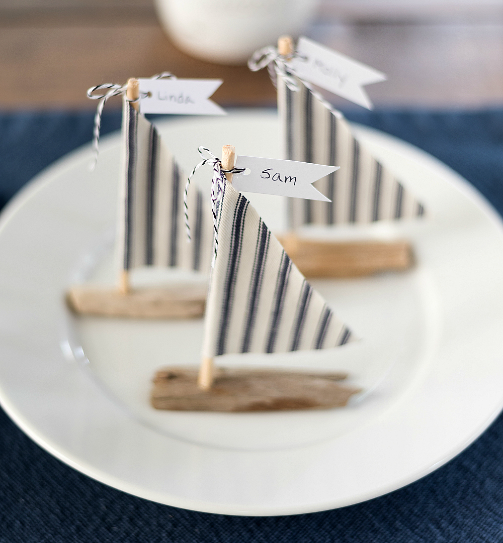 Nautical wedding place setting idea with driftwood sailboats
