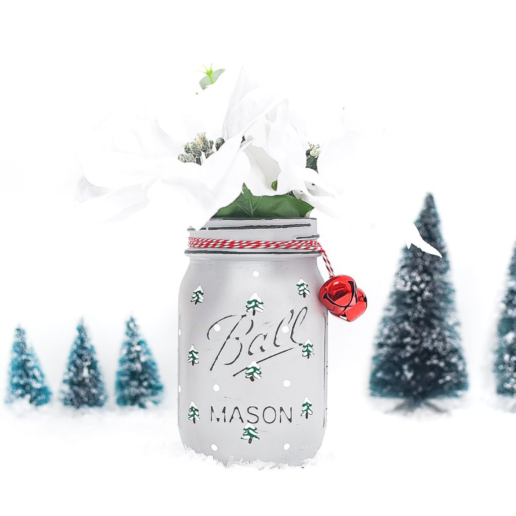 Painted snowy tree mason jar. Christmas tree mason jar craft. How to paint evergreen trees on mason jars. How to paint snowy Christmas trees. Winter craft mason jar.