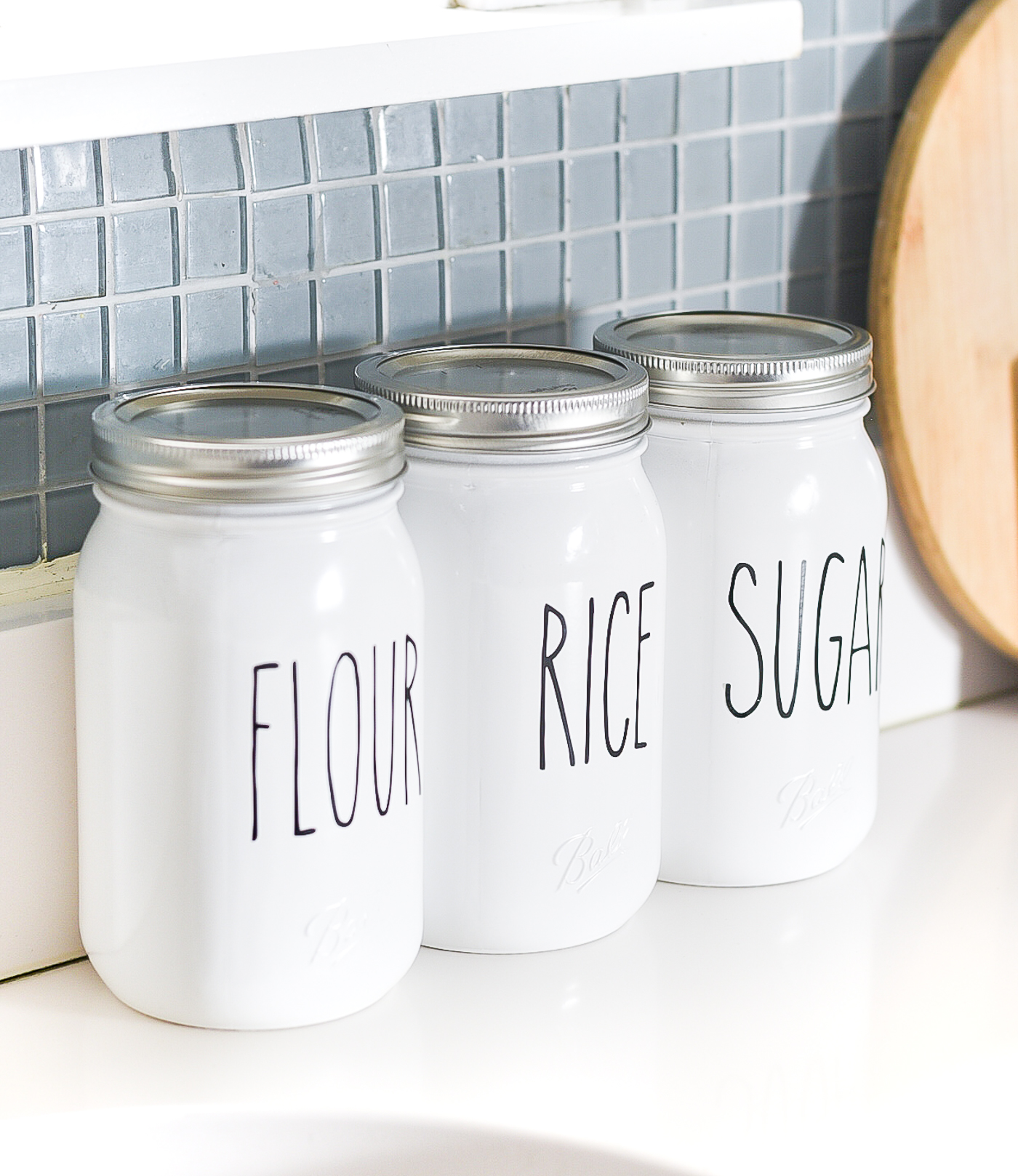 Rae Dunn-inspired mason jar kitchen canisters. Mason jar canister ideas. How to make Rae Dunn pottery, porcelain, canisters. DIY Rae Dunn masons jars.
